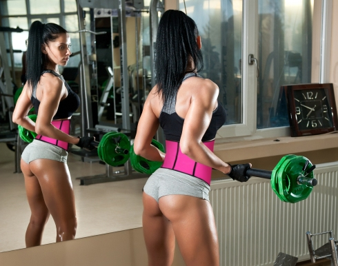Gorgeous brunette working on her muscles in a gym, mirror reflection. Fitness woman doing workout. Sporty girl doing exercise in fitness center. Beautiful brunette toning her muscles at the gym